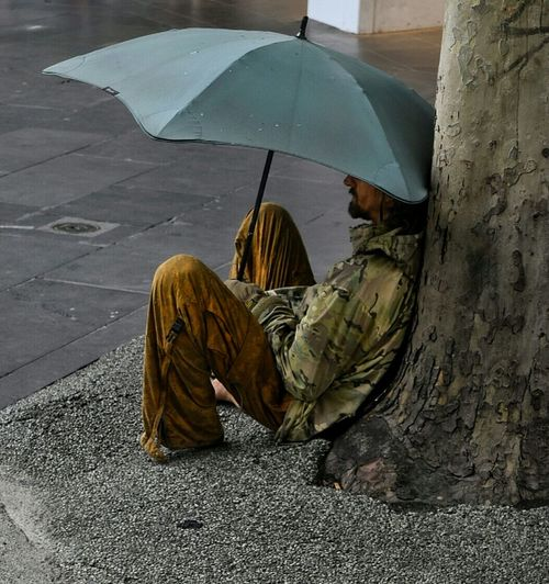 People Watching Umbrella Seated On The Streets Relaxed Shelter Sheltered Taking A Break Man Vagrant Vagrancy Melbourne Bourke St - Melbourne Australia Chilling Road EyeEm Gallery Interesting Pastel Power Sitting Individuality Original A Man In The City Eye4photography