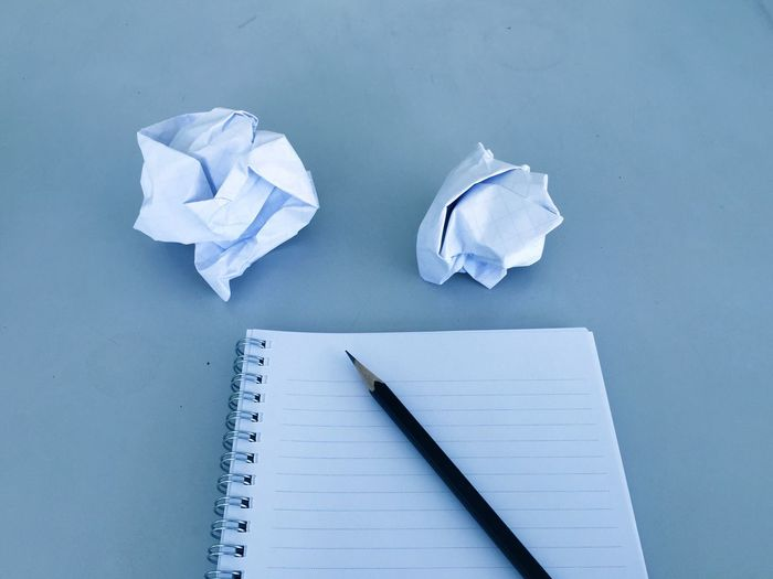 High angle view of crumpled paper balls and book with pencil on blue background