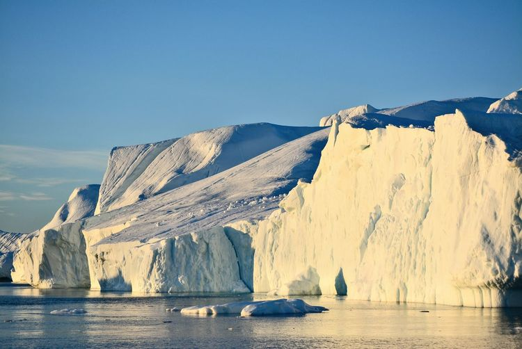 View of majestic iceberg in sea against sky