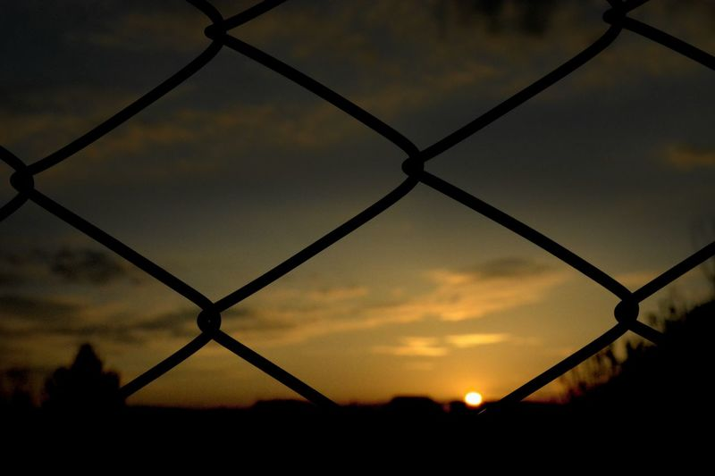 Close-up of silhouette chainlink fence against sky at sunset