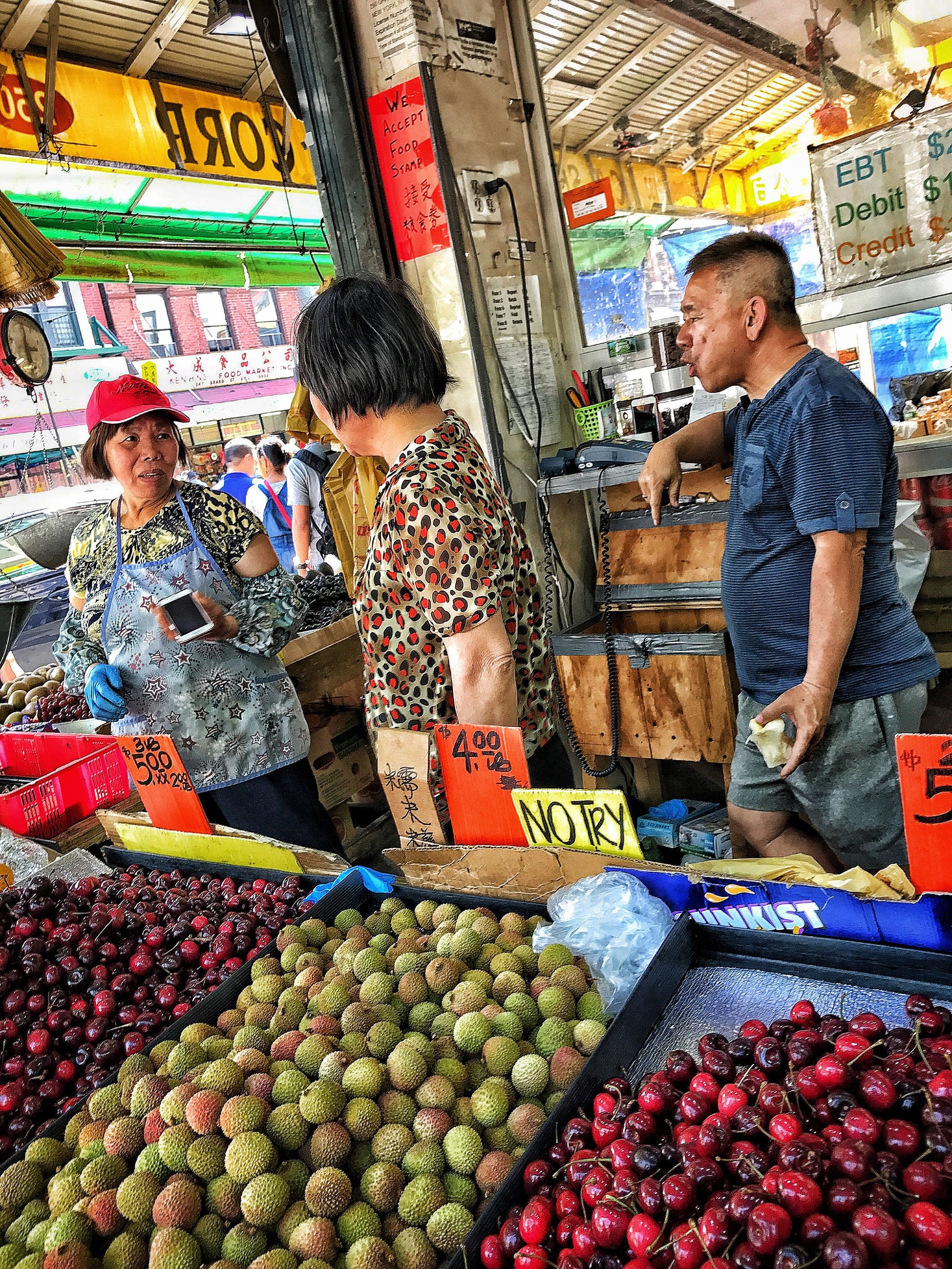 market, food and drink, market stall, fruit, retail, customer, food, day, casual clothing, buying, choice, real people, price tag, outdoors, healthy eating, freshness, men, lifestyles, women, young adult, supermarket, adult, adults only, young women, people