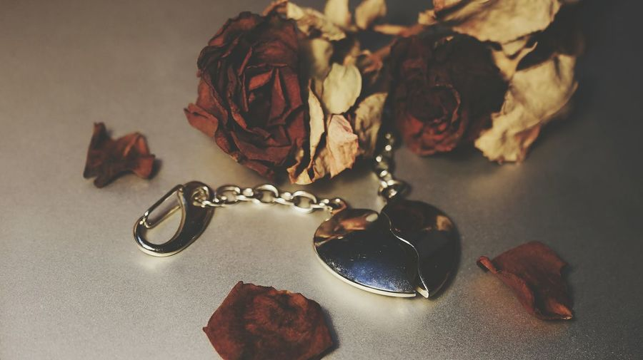 Close-up of heart shape locket and wilted flowers on floor