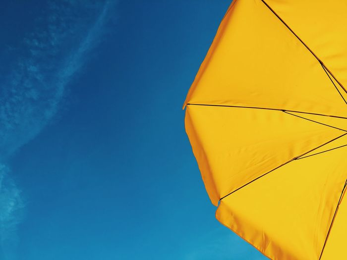 Low Angle View Of Yellow Parasol Against Blue Sky