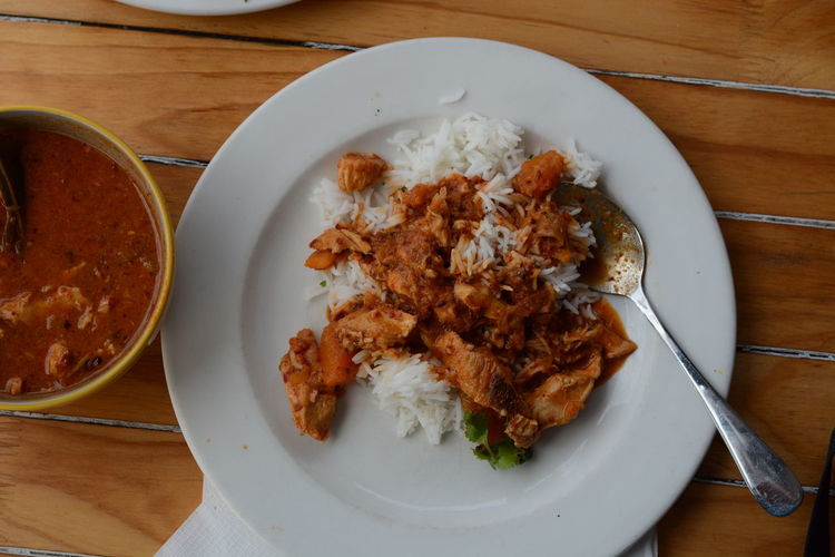 High angle view of rice and meat in plate on table