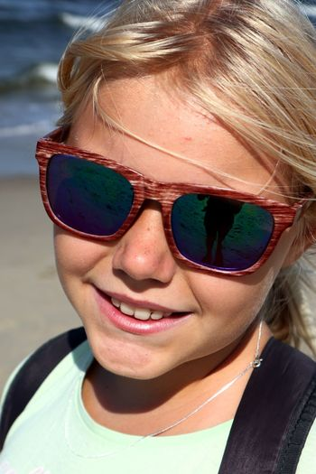 Close-up portrait of smiling girl at beach