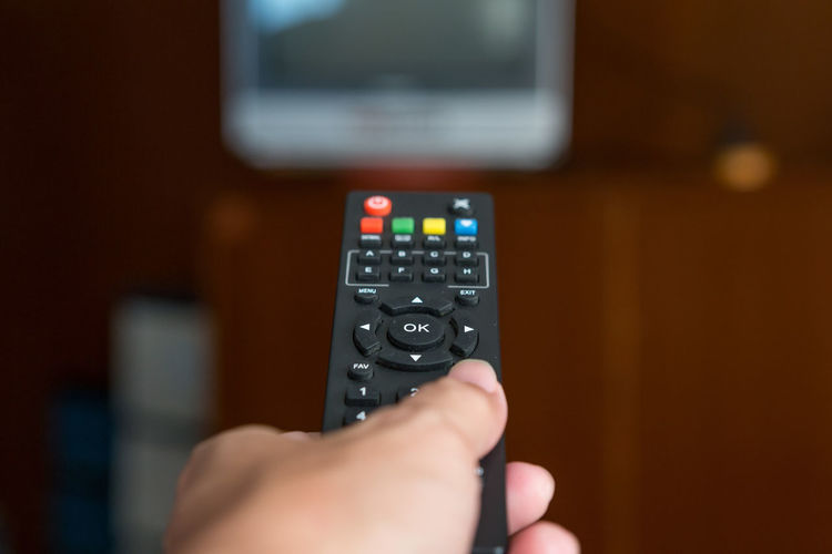 Remote TV in hand on background blurred Body Part Changing Channels Close-up Communication Connection Control Finger Flat Screen Hand Holding Human Body Part Human Hand Indoors  Keypad One Person Push Button Remote Remote Control Technology Television Set Television Show Tv Watching Tv