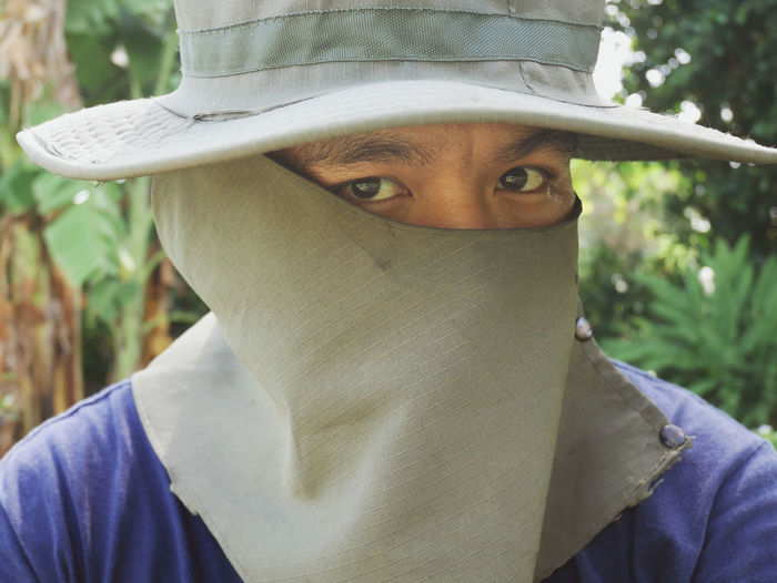 A Man show eye portrait close up. One Person Portrait Headshot Real People Leisure Activity Front View Close-up Lifestyles Looking At Camera Obscured Face Day Human Body Part Unrecognizable Person Focus On Foreground Body Part Young Adult Human Face Hat Teenager
