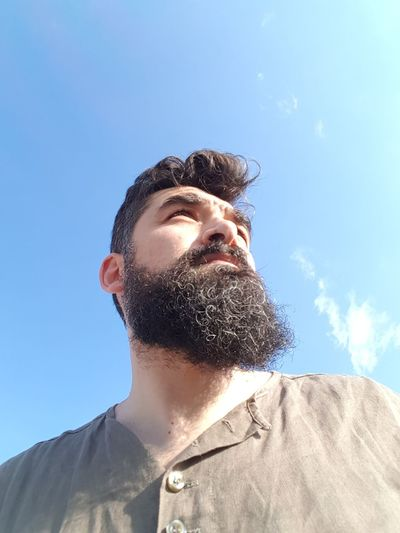 Low angle view of bearded man against sky