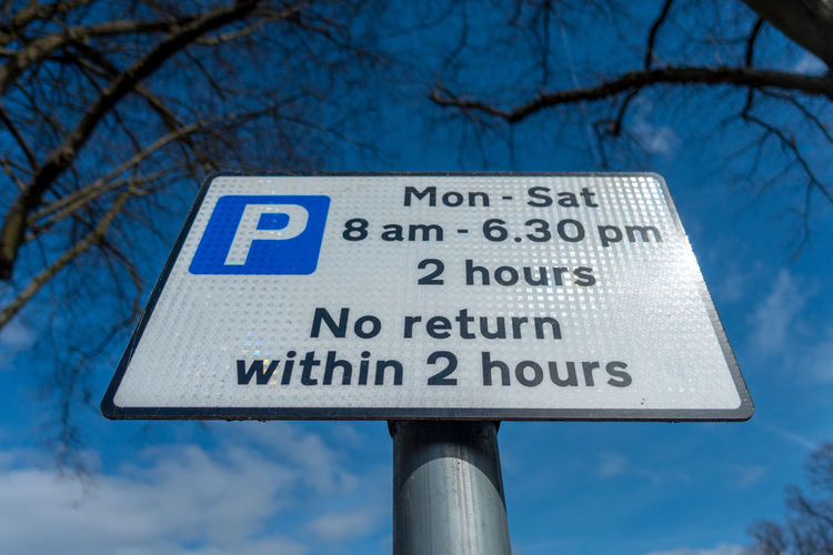 A sign giving information about parking restrictions. Blue Blue Sky Close-up Communication Day Guidance Information Low Angle View No People Outdoors Parking Parking Restrictions Public Notice Road Sign Sign Post Signpost Sky Text