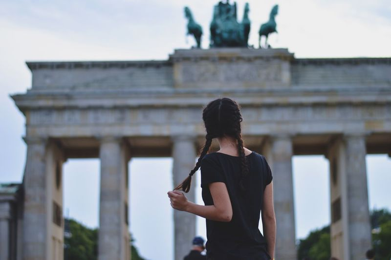 Rear view of woman standing in front of brandenburg gate