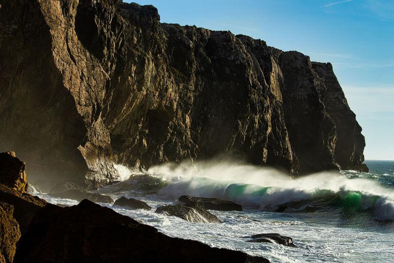 Sea waves splashing on rock against sky
