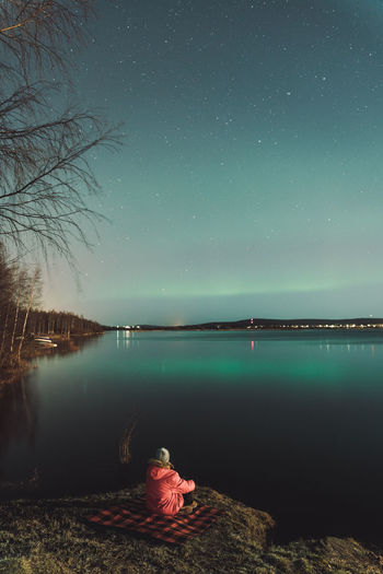 Rear view of man sitting by lake against sky at night