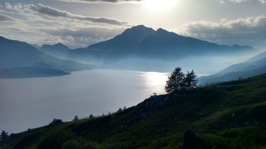 Scenic view of lake and mountains against sky during foggy weather