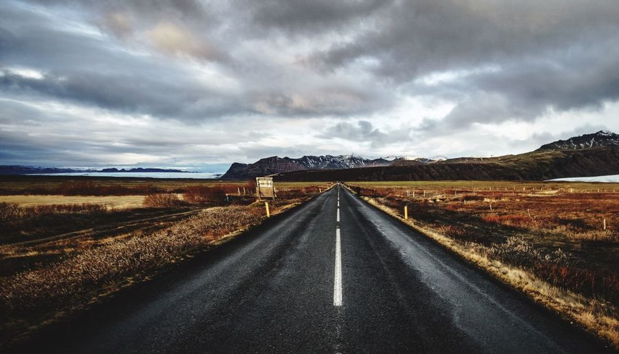 Road amidst landscape against dramatic sky