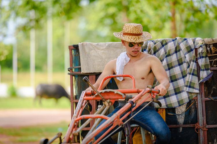 Shirtless man riding agricultural machinery at farm