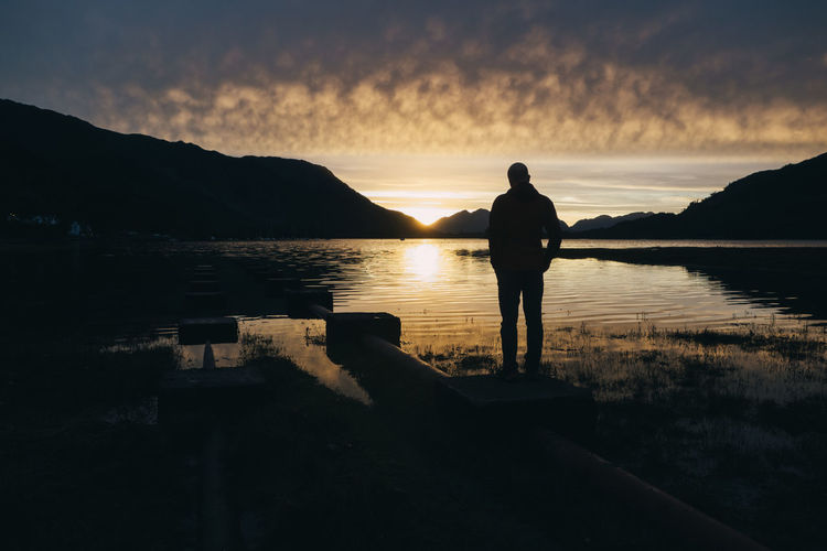 Calm Calmness Glencoe Golden Peace Quiet Quiet Moments Scotland Beauty In Nature Lake Mountain Nature One Person Outdoors Peaceful Real People Reflection Scenics Silhouette Standing Sunset Tranquil Scene Tranquility Travel Destinations Water