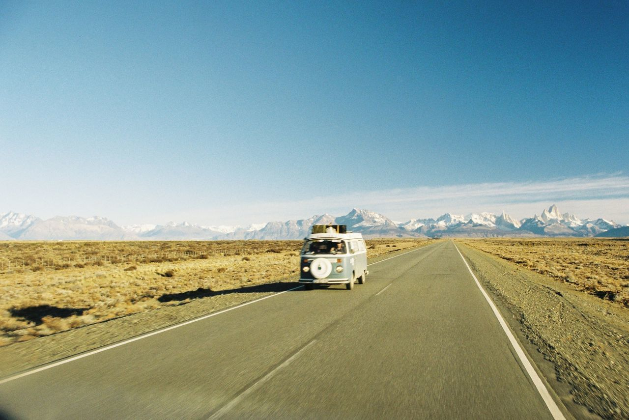 Travel trailer moving on road against sky