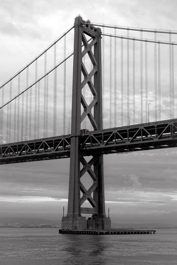 Oakland bay bridge over sea against sky