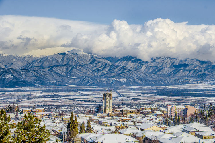 Aerial View Of Cityscape And Mountains Against Sky During Winter
