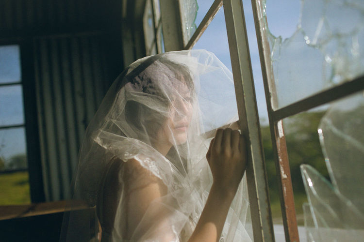 Thoughtful woman covered with fabric by window