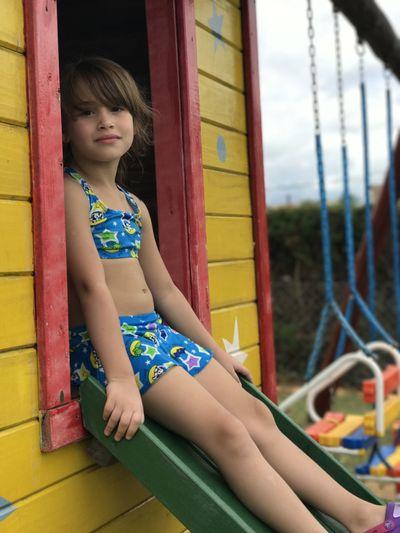 Portrait of girl sitting on slide at playground