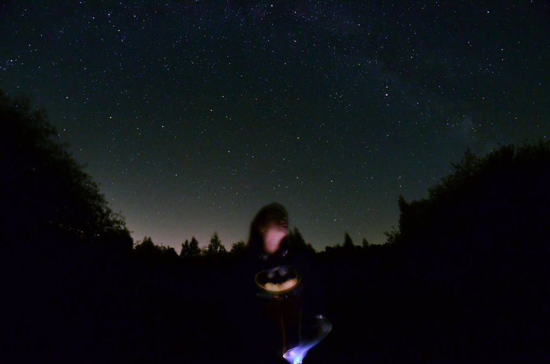 Silhouette woman photographing against clear sky at night
