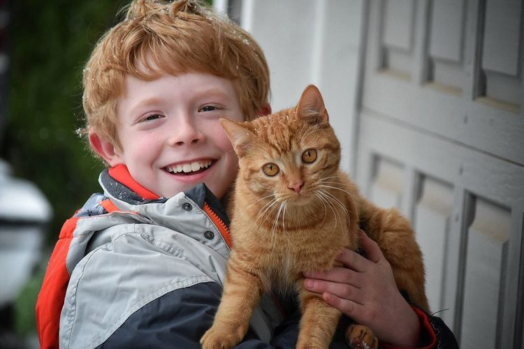 Portrait Of Smiling Boy Holding A Cat