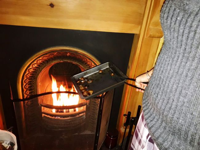 Chestnuts on an open fire One Person Close-up Architecture Built Structure Heat - Temperature Illuminated Flame Indoors  Roadting Tray Food Roasting Chestnuts Open Fire Cooking Woman About To Put Chestnuts On The Fire To Roast Family Time ♥ Autumn Mood