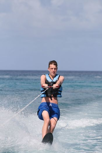 Young man wakeboarding in sea against sky