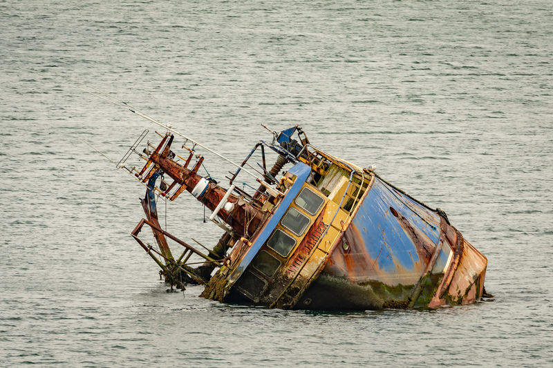 Abandoned ship sinking in sea