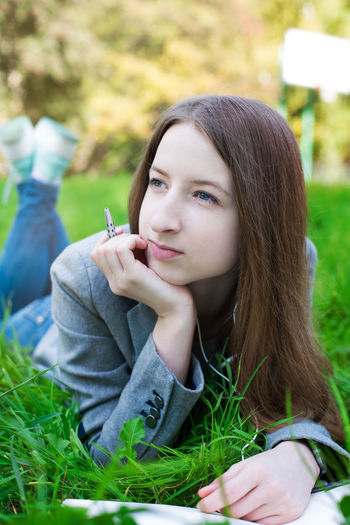 Young Woman Relaxing On Grassy Field