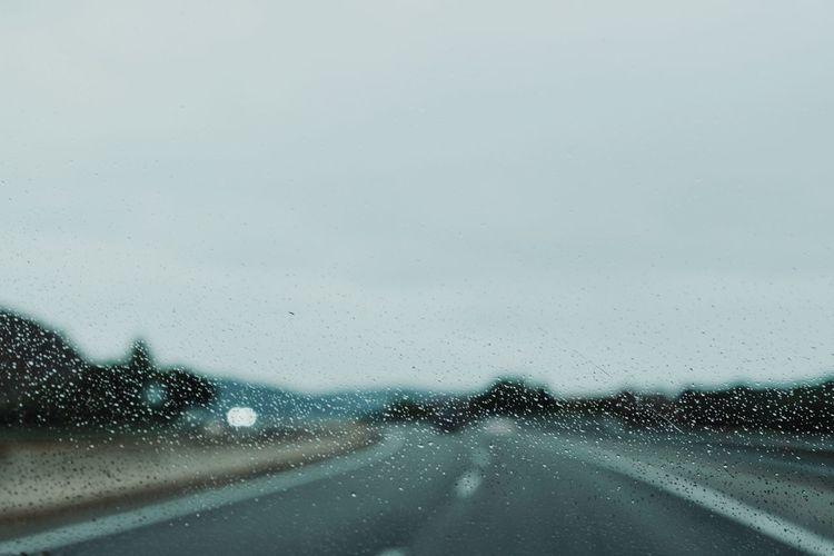 Road seen through wet windshield during rainy season