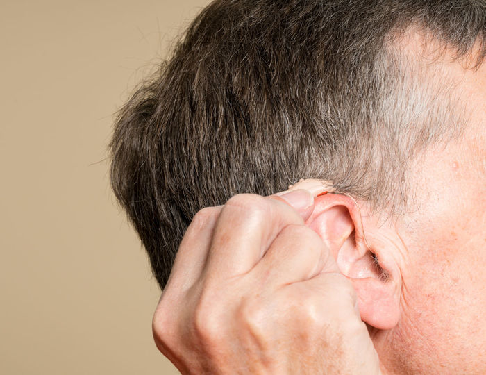Modern small hearing aid fitted behind the ear of a senior adult man Audio Audiology HEAD Man Modern Adult Amplification Behind The Ear Ear Hearing Hearing Aid Hearing Loss One Person Senior Adult Speaker Technology