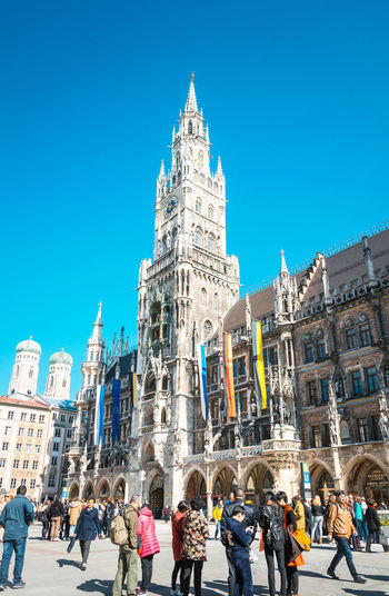 Architecture Blue Building Exterior Built Structure Capital Cities  City City Hall City Life Crowd Day Façade Famous Place Group Of People History Large Group Of People Leisure Activity Lifestyles Marienplatz Mixed Age Range Outdoors Tall - High Tourism Tourist Travel Destinations Vacations