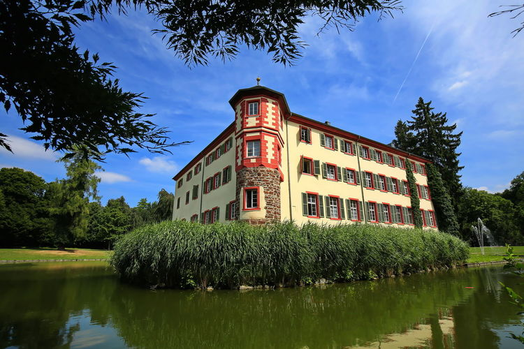 View of building by lake against sky