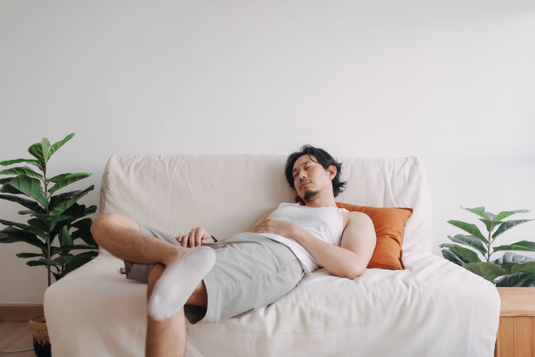 Young man sitting on sofa at home