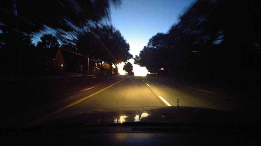 Illuminated road amidst trees against sky at night