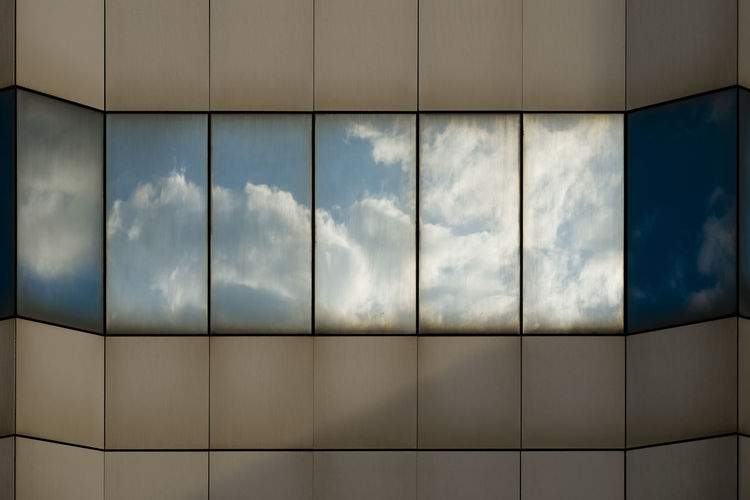 Reflection Of Cloudy Sky On Modern Building