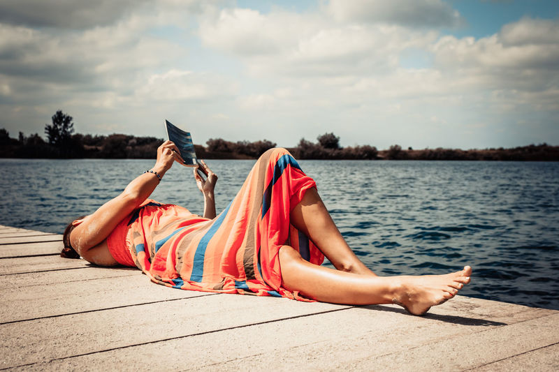 Carefree woman reading book on a pier during summer day.