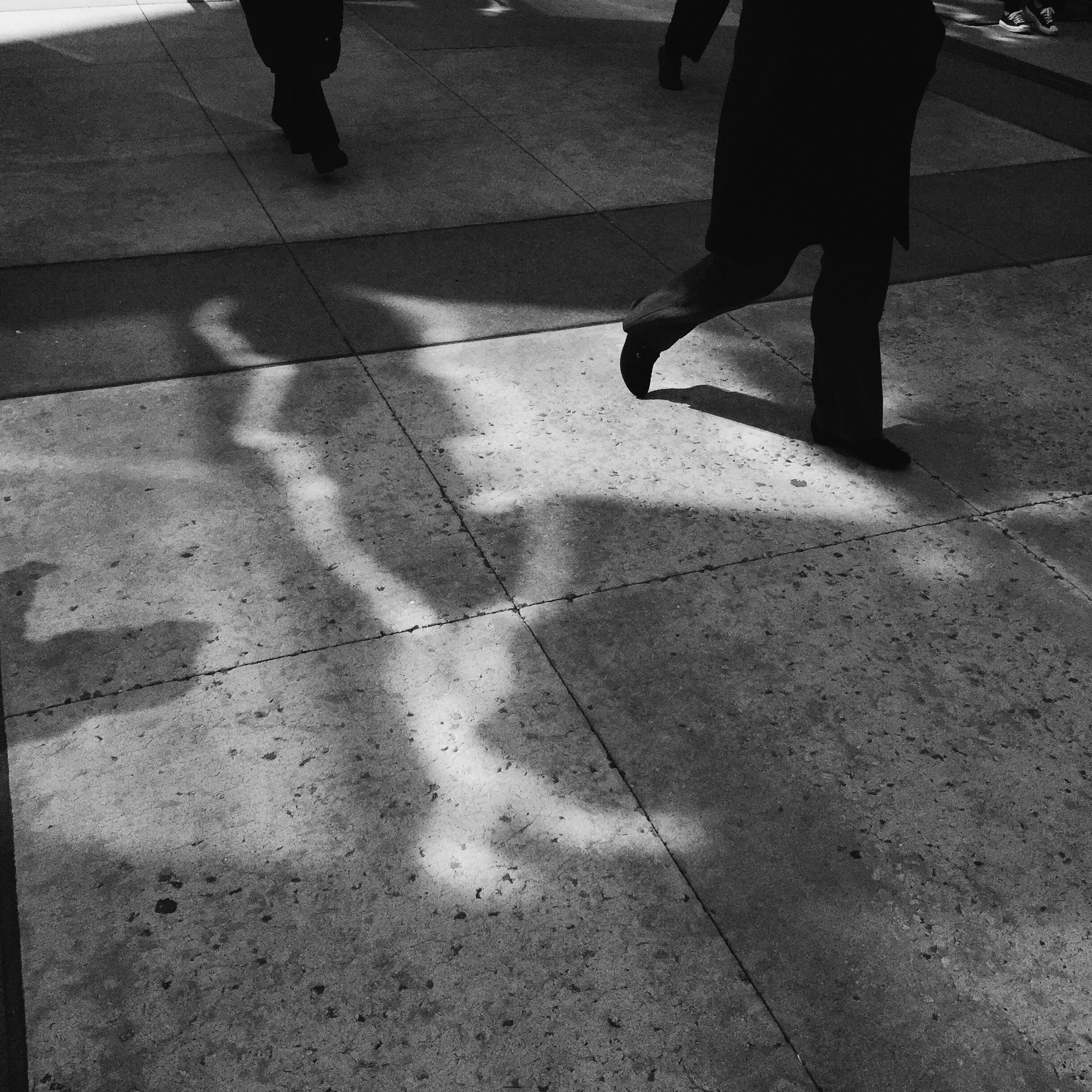 low section, person, walking, lifestyles, street, men, shadow, standing, leisure activity, sunlight, road, on the move, human foot, road marking, city life