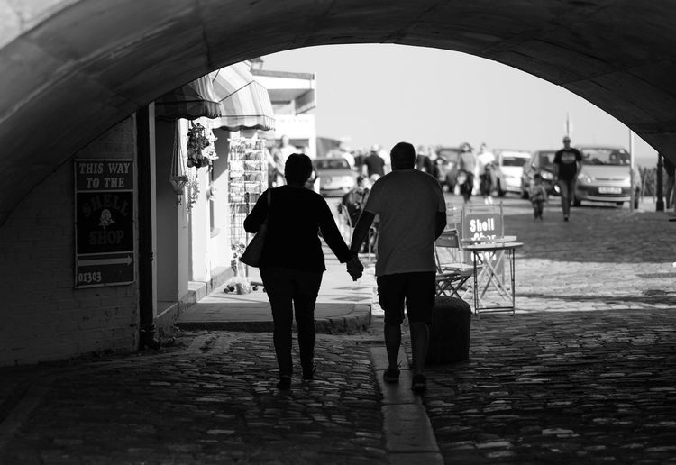 Rear View Of Couple Walking Under Archway