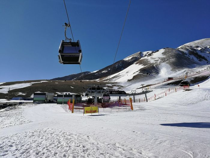 Snow Cold Temperature Winter Mountain Sky Snowcapped Mountain Ski Lift Scenics - Nature Transportation Clear Sky Nature Beauty In Nature Day Environment Mountain Range Overhead Cable Car Incidental People Mode Of Transportation Outdoors Ski Resort  Cableway Ski Run Roccaraso Gravare Ski Area