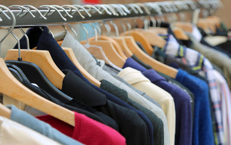 Row of clothes hanging on rack in store