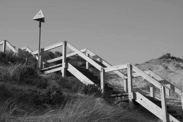 Stairs Architecture Beach Stairs Black And White Blackandwhite Bridge Bridge - Man Made Structure Built Structure Clear Sky Connection Copy Space Day Field Grass Land Nature No People Outdoors Plant Railing Sky Water Wood - Material