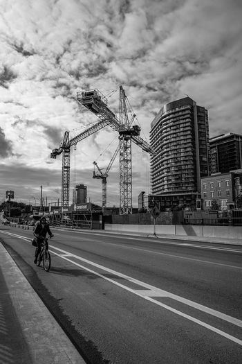 green urban mode of transportation Blackandwhite Monochrome Construction Crane Bike person Bycicle City Arts Culture And Entertainment Cityscape Sky Architecture Skyscraper Office Building Downtown High Rise