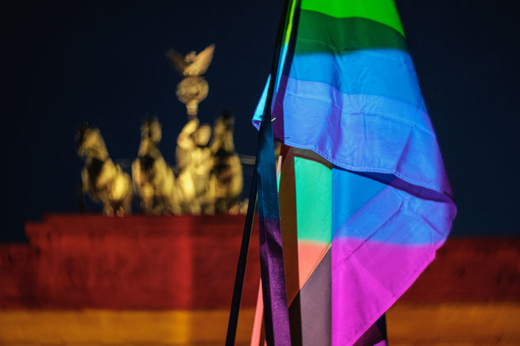 Rainbow flag against brandenburg gate in city at night