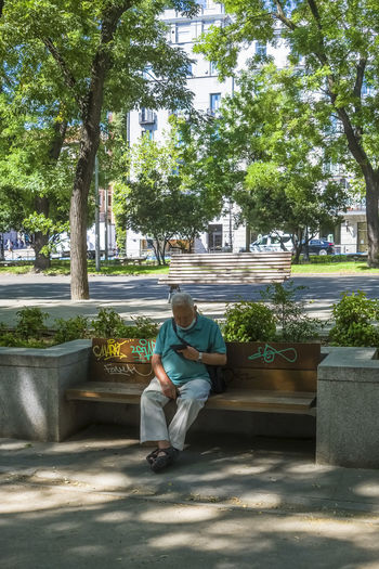 Man sitting on seat against trees