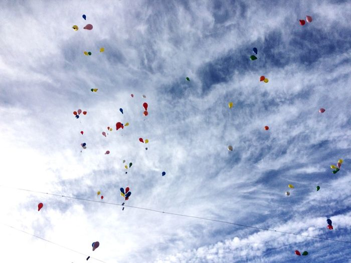Low angle view of colorful helium balloons flying against cloudy sky