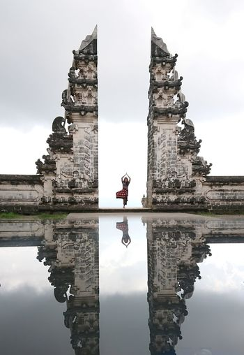 Woman practicing yoga at entrance with reflection in pool