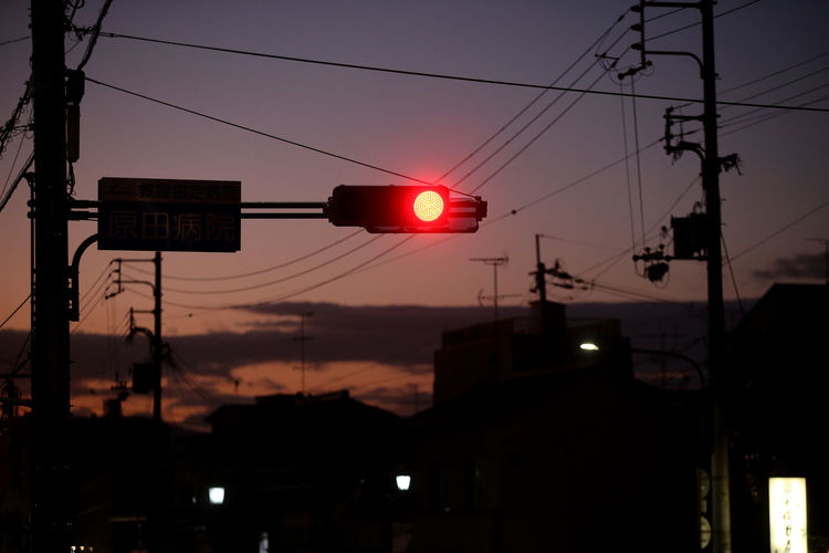 Low angle view of traffic lights against sky during sunset